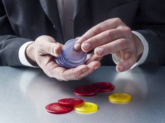 business man playing with casino chips at his desk