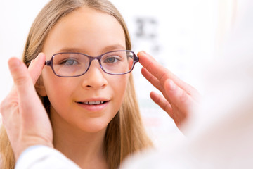 Young little girl trying glasses at the optician