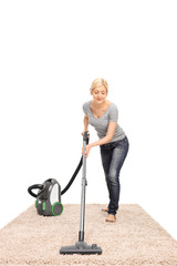 Young housewife vacuuming a carpet