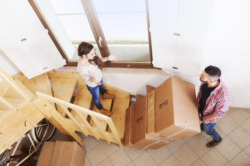 young couple carrying the boxes in new house