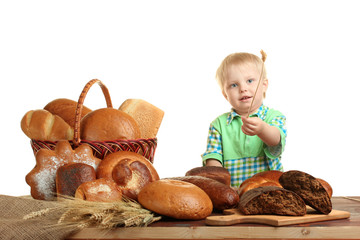 little boy at a full table of bread holding spike