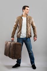 Tourist holding his suitcase, studio portrait