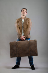 Tourist holding his suitcase, studio portrait