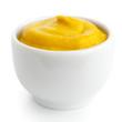 Small white ceramic dish of American mustard. Isolated.