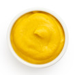 American yellow mustard in round dish from above on white. - 80784595