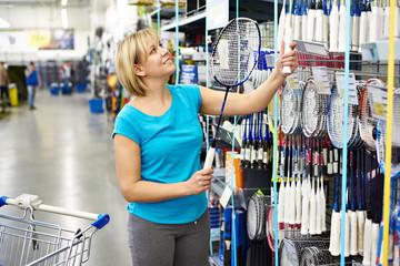 Woman chooses badminton racquet in shop