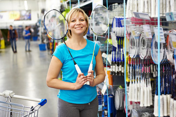 Woman chooses badminton racquet in shop