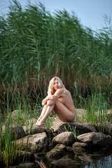 naked woman sitting on the stones against green reeds
