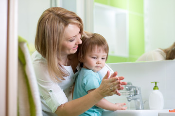 child boy washing hands with soap in bathroom