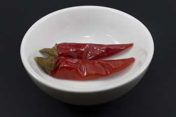 pickled chilis in a white bowl on a black background.