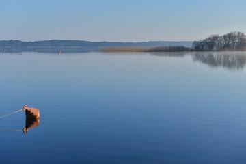 Mooring buoy on a lake at sunrise.