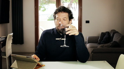 Handsome man enjoying glass of wine while reading on ipad