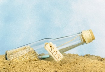 A glass bottle with SOS in sand on a blue background