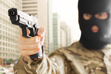 Man in black mask holding gun with city on background