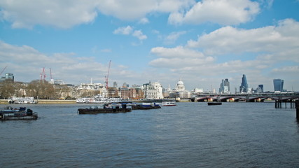 boats travel on river thames in london. Cityscape in the backgro