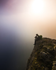 man sitting on a cliff in foggy weather