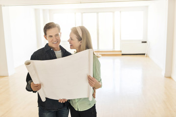 Happy Mature Couple With Blueprint At New Home