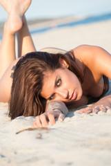 Beautiful model lying in sand on a beach