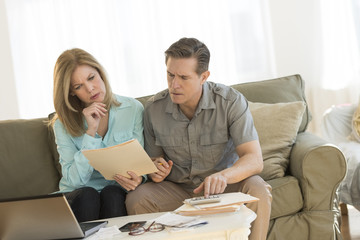 Mature Couple Calculating Home Finances On Sofa