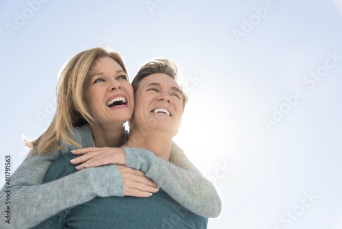 Poster Man Giving Piggyback Ride To Woman Against Clear Sky