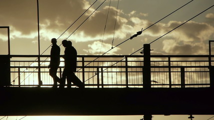 Silhouettes of people crossing the railroad on old metal bridge