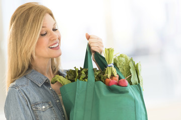Mature Woman Carrying Shopping Bag Full Of Vegetables