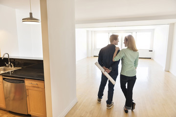 Rear View Of Couple Standing In New House