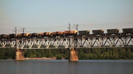 Cargo train on the bridge crossing the river