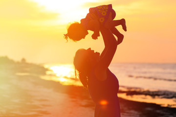 mother and little daughter play at sunset