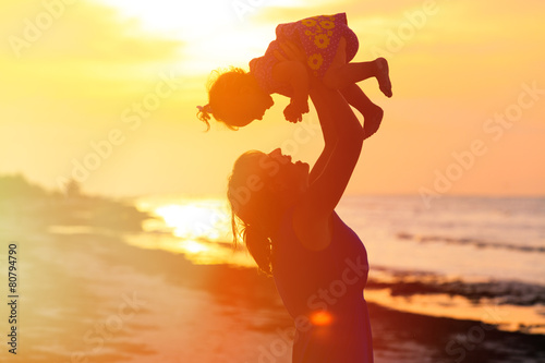 mother and little daughter play at sunset - 80794790