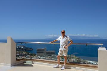 Man is standing at terrace in Los Gigantes resort, Tenerife.