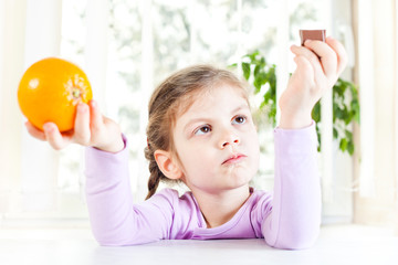 Little girl holding orange and chocolate, fruit or candy dilemma