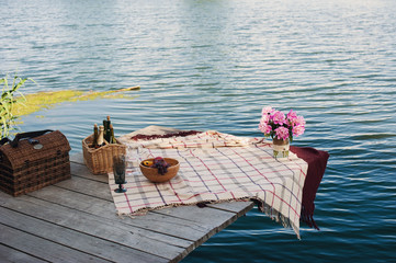 Picnic baskets with plaids on the pier and bouquet
