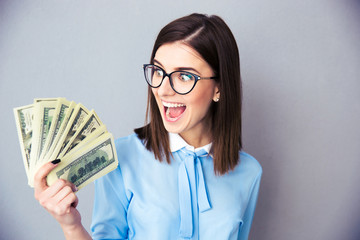 Cherrful businesswoman holding bill of dollars