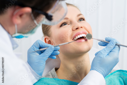Male dentist examining patient teeth before oral operation