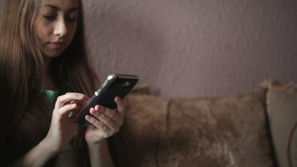 Woman sitting on sofa and looking at smartphone