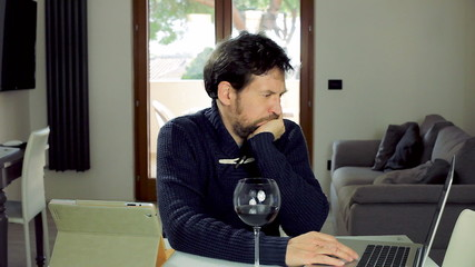 Handsome man working with computer at home serious
