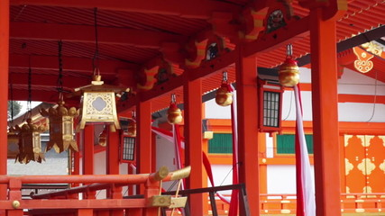 Bells with ropes hang on red shrine of temple in Kyoto Japan