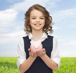 happy girl holding piggy bank on palms