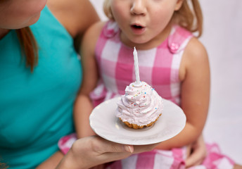 happy mother and girl blowing out cupcake candle