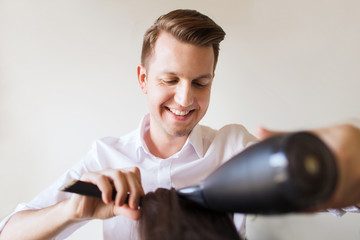 happy stylist with fan making blow-dry at salon