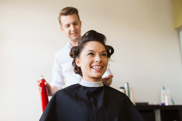happy woman with stylist making hairdo at salon