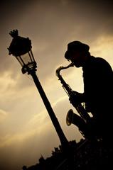 Saxophoniste sur le pont des Arts à Paris en contre jour