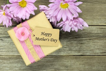 Gift box with Happy Mothers Day tag on rustic wood with daisies