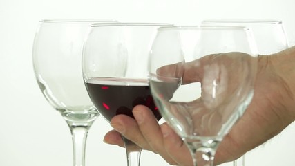 Pouring of red wine in a transparent glass   on white