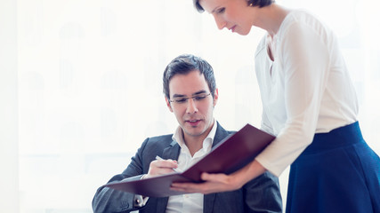 Businesswoman standing in the office presenting a document in a