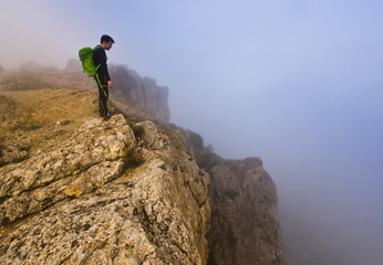 man standing on a cliff in foggy weather