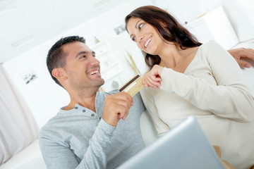 Playful couple arguing over on-line shopping