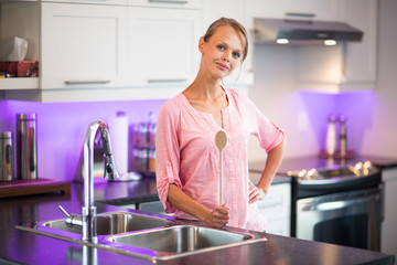 Pretty, young woman posing in her modern kitchen