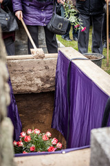 Mourners staying by the opened grave, burrying at a cemetery